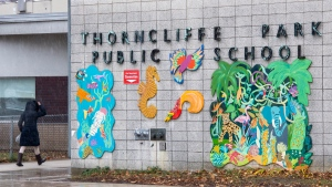 A woman wakls into Thorncliffe Park Public School in Toronto on Monday November 30, 2020. . THE CANADIAN PRESS/Frank Gunn