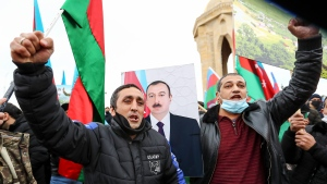Azerbaijanis with national flags and a portrait of Azerbaijani President Ilham Aliyev celebrate returning their territories in Baku, Azerbaijan, Tuesday, Dec. 1, 2020. Azerbaijan has completed the return of the territories ceded by Armenia under a Russia-brokered peace deal that ended six weeks of fierce fighting over Nagorno-Karabakh. Azerbaijan's President Ilham Aliyev hailed the restoration of control over the Lachin region and other territories as a historic achievement. (AP Photo/Aziz Karimov)