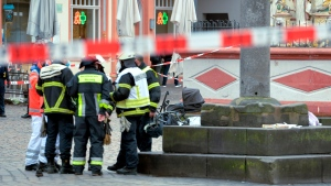 Firefighters stay together at the scene of an incident in Trier, Germany, Tuesday, Dec. 1, 2020. German police say people have been killed and several others injured in the southwestern German city of Trier when a car drove into a pedestrian zone. Trier police tweeted that the driver had been arrested and the vehicle impounded. (Harald Tittel/dpa via AP)