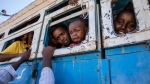 Tigray refugees who fled the conflict in the Ethiopia's Tigray ride a bus going to the Village 8 temporary shelter, near the Sudan-Ethiopia border, in Hamdayet, eastern Sudan, Tuesday, Dec. 1, 2020. (AP Photo/Nariman El-Mofty)
