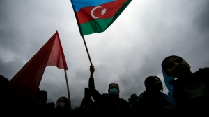Azerbaijani wave national flags as they celebrate the transfer of the Lachin region to Azerbaijan's control, as part of a peace deal that required Armenian forces to cede the Azerbaijani territories they held outside Nagorno-Karabakh, in Aghjabadi, Azerbaijan, Tuesday, Dec. 1, 2020. (AP Photo/Emrah Gurel)