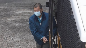 Jimmy Lai of Next Digital, which publishes the Apple Daily newspaper, is escorted by Correctional Services officers to prison, in Hong Kong, Thursday, Dec. 3, 2020. Outspoken Hong Kong pro-democracy advocate and media tycoon Lai was refused bail on Thursday on a fraud charge amid a growing crackdown on dissent in the semi-autonomous city. (AP Photo/Kin Cheung)
