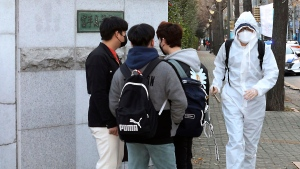 An examinee wearing a protective suit arrives to take the college entrance exams at a high school in Incheon, South Korea, Thursday, Dec. 3, 2020. Hundreds of thousands of masked students in South Korea, including dozens of confirmed COVID-19 patients, took the highly competitive university entrance exam Thursday despite a viral resurgence that forced authorities to toughen social distancing rules. (Lee Jong-chul/Newsis via AP)