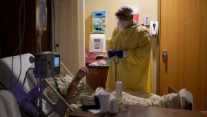 In this Nov. 24, 2020, file photo, Dr. Shane Wilson performs rounds in a portion of Scotland County Hospital set up to isolate and treat COVID-19 patients in Memphis, Mo. Across the U.S., the surge has swamped hospitals with patients and left nurses and other health care workers shorthanded and burned out. (AP Photo/Jeff Roberson)