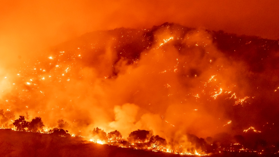 The Bond Fire, driven by high winds, burns the hillsides west of Santiago Canyon Road near Silverado Canyon, Calif., on Thursday, Dec. 3, 2020. (Leonard Ortiz/The Orange County Register via AP)