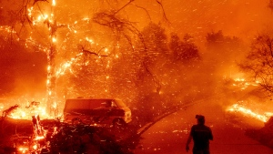 Bruce McDougal watches embers fly over his property as the Bond Fire burns through the Silverado community in Orange County, Calif., on Thursday, Dec. 3, 2020. (AP Photo/Noah Berger)