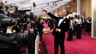 FILE - Tom Hanks arrives at the Oscars in Los Angeles on Feb. 9, 2020. Hollywood's awards season has gone virtual. This time of year would normally be flush with splashy premieres, cocktail parties and star-studded screening. This year, Oscar campaigns are having to make do with virtual Q&As and home-delivered gift baskets. (Photo by Jordan Strauss/Invision/AP, File)