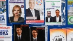 Electoral posters are placed on a board in Bucharest, Romania, Thursday, Dec. 3, 2020. Romania will hold parliamentary elections on Sunday Dec. 6. (AP Photo/Andreea Alexandru)