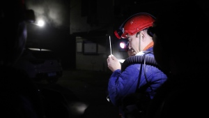 In this photo released by Xinhua News Agency, a rescue worker gauges the density of carbon monoxide in the smog at the entrance of the coal mine in Yongchuan District of Chongqing, southwestern China, Dec. 4, 2020. China's state TV says more than a dozen coal miners have been killed by high levels of carbon monoxide in the country's southwest. (Huang Wei/Xinhua via AP)