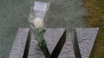 A white rose is placed on the monument remembering Maryse Laganiere at the Place du 6-Decembre-1989 in Montreal, on Friday, Dec. 4, 2020. Laganiere is one of 14 women murdered in an antifeminist attack at Ecole Polytechnique on December 6, 1989. THE CANADIAN PRESS/Paul Chiasson