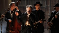 "In this Feb. 13, 2011, file photo, Bob Dylan, center, performs at the 53rd annual Grammy Awards in Los Angeles. Dylan won the 2016 Nobel Prize in literature on Thursday, Oct. 13, 2016, a stunning announcement that for the first time bestowed the prestigious award on a musician for ""having created new poetic expressions within the great American song tradition."" (AP Photo/Matt Sayles, File)"