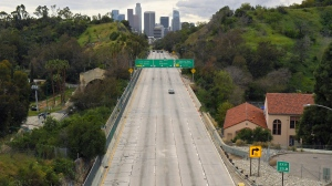 FILE - In this Friday, March 20, 2020 file photo, extremely light traffic moves along the 110 Harbor Freeway toward downtown Los Angeles in the mid-afternoon. Traffic would normally be bumper-to-bumper during this time of day on a Friday. New calculations released on Thursday, Dec. 10, 2020, show the world's carbon dioxide emissions plunged 7% in 2020 because of the pandemic lockdowns. (AP Photo/Mark J. Terrill)