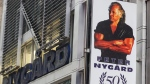 A sign bearing the likeness of Peter Nygard is displayed outside his Times Square headquarters, Tuesday, Feb. 25, 2020, in New York. (AP Photo/John Minchillo)
