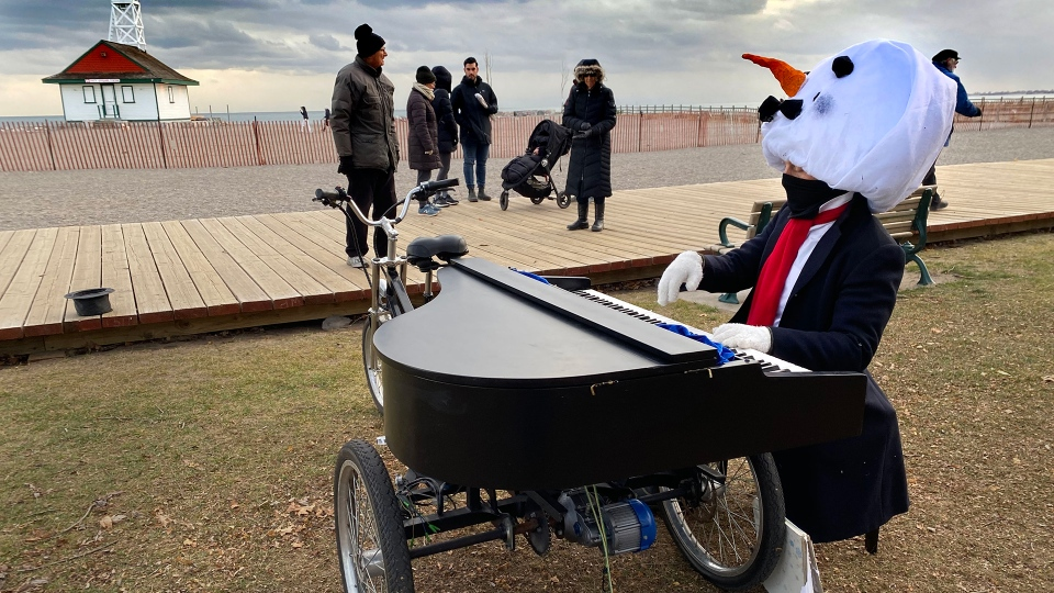 A man wears a snowman headdress as he plays a tricycle drawn piano on the boardwalk in Toronto on Tuesday, Dec. 15, 2020. THE CANADIAN PRESS/Frank Gunn
