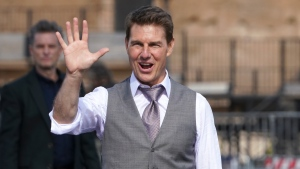 Actor Tom Cruise waves to fans during a break in the shooting of the film Mission Impossible 7, in Rome, Monday, Oct. 12, 2020. (AP Photo/Andrew Medichini)
