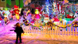 A young child is dwarfed by a large 3-home Christmas light installation in Toronto, Sunday, Nov. 22, 2020. THE CANADIAN PRESS/Frank Gunn