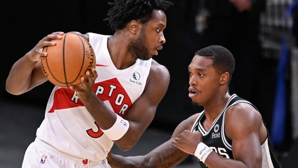 Toronto Raptors' O.G. Anunoby, left, drives against San Antonio Spurs' Lonnie Walker IV during the first half of an NBA basketball game Saturday, Dec. 26, 2020, in San Antonio. (AP Photo/Darren Abate)