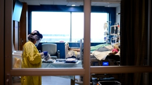 An ICU health-care worker shown inside a negative pressure room cares for a COVID-19 patient on a ventilator at the Humber River Hospital during the COVID-19 pandemic in Toronto on Wednesday, December 9, 2020. THE CANADIAN PRESS/Nathan Denette