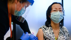 Registered nurse Clair Judd, left, vaccinates LTC nurse Yinghua Fang with the Pfizer-BioNTech COVID-19 mRNA vaccine during the COVID-19 pandemic in Toronto on Tuesday, December 15, 2020.  THE CANADIAN PRESS/Nathan Denette