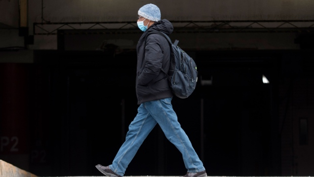 A man wears a face mask as he walks along a street in Montreal, Wednesday, December 30, 2020, as the COVID-19 pandemic continues in Canada and around the world. THE CANADIAN PRESS/Graham Hughes
