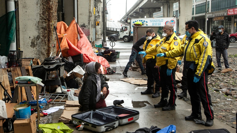 Police officers speak to a homeless person experiencing sitting by a dwelling as city workers clear an encampment on Toronto's Bay Street, Friday, May 15, 2020. Authorities in some provinces ramped up often arbitrary law enforcement to help curtail the COVID-19 pandemic rather than rely on a purely public health approach, according to a report out Wednesday. The main problem, the report finds, is that marginalized or other vulnerable groups tended to bear the brunt of police and bylaw action.  THE CANADIAN PRESS/Chris Young
