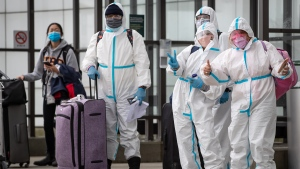 People wearing protective face masks, goggles and Tyvek suits who said they traveled from Colombia gesture while waiting for a car rental company shuttle, after arriving at Vancouver International Airport in Richmond, B.C., on Thursday, December 31, 2020. Beginning January 7, air travellers arriving in Canada will be required to provide proof of a negative COVID-19 test conducted within 72 hours of boarding the plane. THE CANADIAN PRESS/Darryl Dyck