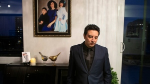Alireza Ghandchi is photographed in front of a portrait of his wife Faezeh, daughter Dorsa and son Daniel in Richmond Hill, Ont., Friday, January 1, 2021. Ghandchi lost his family after Iranian forces shot down a Ukrainian passenger jet on Jan. 8, 2020. THE CANADIAN PRESS/Chris Young