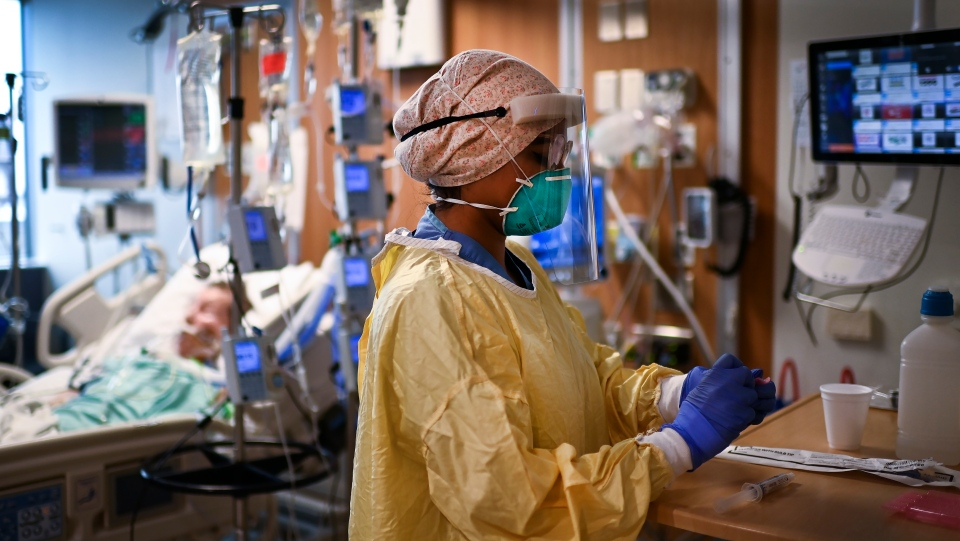 ICU health-care worker Jannikka Navaratnam cares for a patient inside a negative pressure room at the Humber River Hospital during the COVID-19 pandemic in Toronto on Wednesday, December 9, 2020. THE CANADIAN PRESS/Nathan Denette