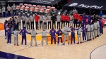 Members of the Phoenix Suns and the Toronto Raptors form a circle during the American national anthem prior to a basketball game Wednesday, Jan. 6, 2021, in Phoenix. (AP Photo/Ross D. Franklin)