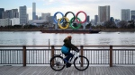 A man rides a bicycle near the Olympic rings floating in the water in the Odaiba section Friday, Jan. 8, 2021 in Tokyo. (AP Photo/Eugene Hoshiko)