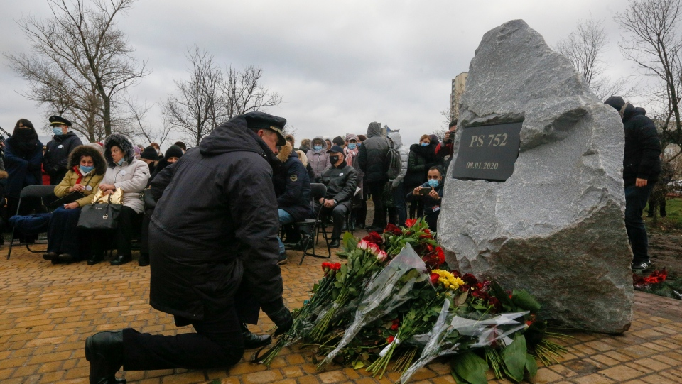A pilot lays flowers to a memorial in Kyiv, Ukraine, Friday, Jan. 8, 2021, for the victims of a Ukrainian 737-800 plane crash on the outskirts of Tehran. One year after Iranian forces shot down a Ukrainian jetliner, killing all 176 people on board, more questions remain than answers as families of victims allege harassment by Iranian authorities and affected countries raise concerns about the lack of transparency and accountability in Iran's investigation. (AP Photo/Efrem Lukatsky)