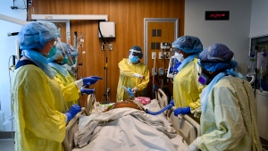 Health-care workers plan on how to turn a COVID-19 patient in the ICU who is intubated and on a ventilator from his back to his stomach at the Humber River Hospital during the COVID-19 pandemic in Toronto on Wednesday, December 9, 2020. THE CANADIAN PRESS/Nathan Denette