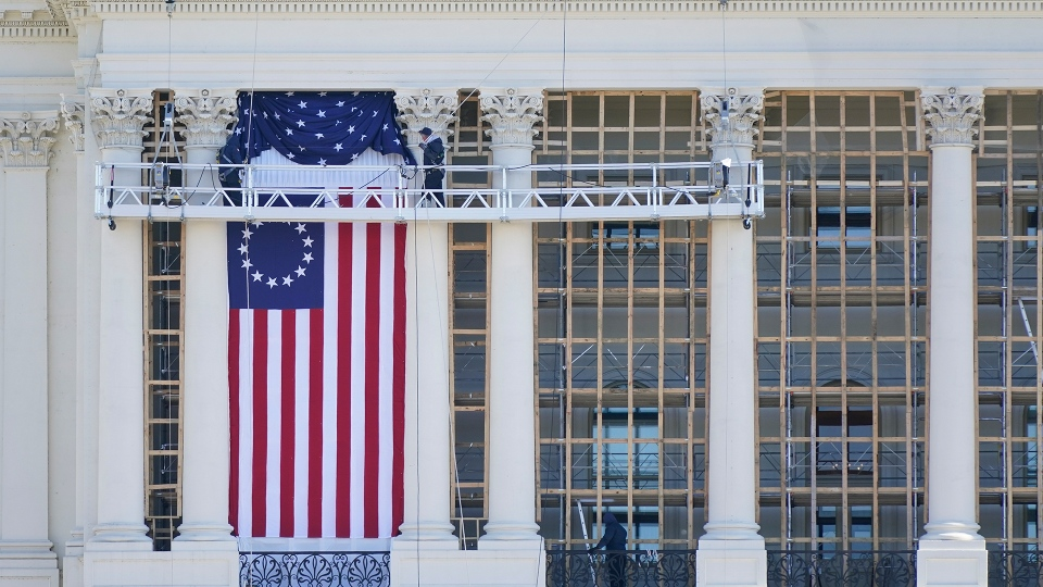 Workers install a flag on the West Front of the U.S. Capitol as preparations take place for President-elect Joe Biden's inauguration, Saturday, Jan. 9, 2021, in Washington. (AP Photo/Patrick Semansky)