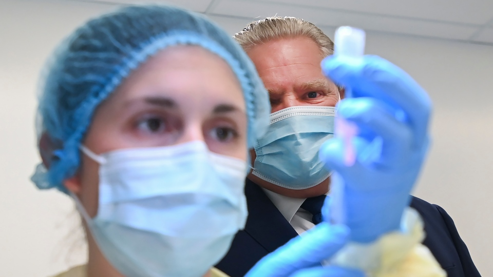 Ontario Premier Doug Ford watches a health-care worker prepare a dose of the Pfizer-BioNTech COVID-19 vaccine at a UHN vaccine clinic in Toronto on Thursday, January 7, 2021. THE CANADIAN PRESS/Nathan Denette