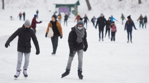 People wear face masks as they skate on a lake in a city park in Montreal, Sunday, January 10, 2021, as the COVID-19 pandemic continues in Canada and around the world. The Quebec government has imposed a lockdown and a curfew to help stop the spread of COVID-19. The curfew begins at 8 p.m. until 5 a.m. and lasting until February 8. THE CANADIAN PRESS/Graham Hughes