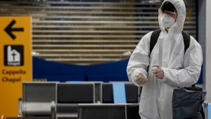 A passenger wearing protective gear sanitizes his hands at Rome's Leonardo da Vinci airport, Wednesday, Dec. 9, 2020. The first Alitalia flight landed in Rome from New York with passengers tested before departure and upon arrival and, as a result, aren't required to undergo the mandatory 14-day quarantine imposed by Italy. (Cecilia Fabiano/LaPresse via AP)