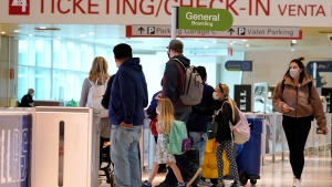 Air travelers process through a security check point at Love Field Airport in Dallas, Tuesday, Nov. 24, 2020. (AP Photo/Tony Gutierrez)