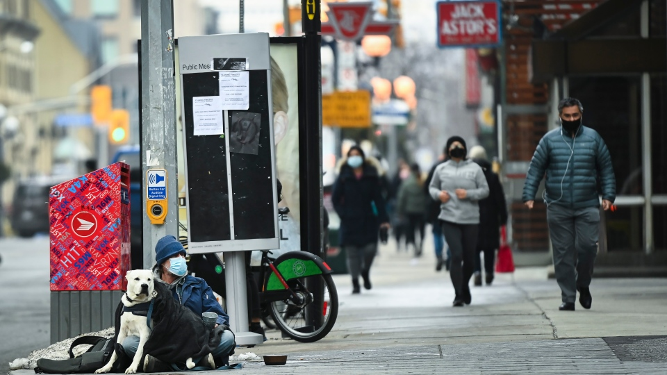 A homeless person wearing a mask sits with his dog as people go about their daily lives during the COVID-19 pandemic in Toronto on Thursday, January 14, 2021. The province of Ontario is currently under an emergency order lockdown. THE CANADIAN PRESS/Nathan Denette