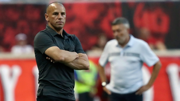 FILE - New York Red Bulls head coach Chris Armas, left, watches his team from the sideline while New York City FC head coach Domenec Torrent looks on during the second half of an MLS soccer match, Sunday, July 14, 2019, in Harrison, N.J. (AP Photo/Steve Luciano, File)