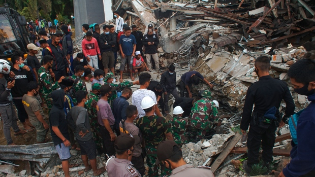 Rescuers search for survivors at the ruin of a government building collapsed during an earthquake in Mamuju, West Sulawesi, Indonesia, Friday, Jan. 15, 2021. A strong, shallow earthquake shook Indonesia's Sulawesi island just after midnight Friday, toppling homes and buildings, triggering landslides and killing a number of people. (AP Photo/Azhari Surahman)