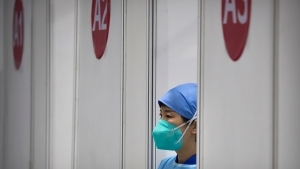A medical worker wearing protective equipment waits for patients at a coronavirus vaccination facility in Beijing, Friday, Jan. 15, 2021. A city in northern China is building a 3,000-unit quarantine facility to deal with an anticipated overflow of patients as COVID-19 cases rise ahead of the Lunar New Year travel rush. (AP Photo/Mark Schiefelbein)