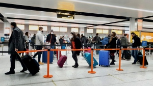 In this Dec. 20, 2020, file photo, passengers queue for check-in at Gatwick Airport in West Sussex, England, south of London. (Gareth Fuller/PA via AP)