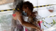 In this Jan. 6, 2021, file photo, Maria Amelia, right, hugs her niece Flaviana Silva through a plastic barrier during a visit to the Casa Clara home for the elderly in Brasilia, Brazil. The global death toll from COVID-19 has topped 2 million. (AP Photo/Eraldo Peres, File)