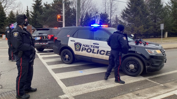 Police are shown blocking off traffic in an Oakville neighbourhood on Friday afternoon.Police say that at least two individuals have barricaded themselves inside a residence. (Tom Podolec)