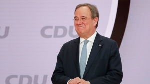 The new elected Christian Democratic Union, CDU, party chairman Armin Laschet stands on the podium after the voting at a digital party convention in Berlin, Germany, Saturday, Jan. 16, 2021. The party of German Chancellor Angela Merkel decided on a successor for the outgoing chairwoman Annegret Kramp-Karrenbauer at the convention. (AP Photo/Markus Schreiber)