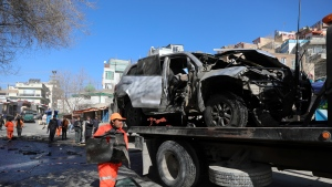 Afghan security personnel remove a damaged vehicle after a bomb attack in Kabul, Afghanistan, Saturday, Jan. 16, 2021. A sticky bomb attached to an armored police Land Cruiser SUV exploded Saturday in the western part of the capital, Kabul, killing few policemen and wounding another, Kabul police spokesman Ferdaws Faramarz said. (AP Photo/Rahmat Gul)