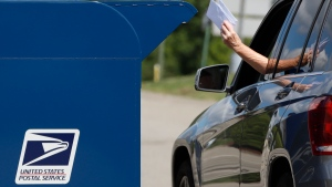 FILE - In this Aug. 19, 2020, file photo, a person deposits mail in a box outside United States Post Office in Cranberry Township, Pa. (AP Photo/Gene J. Puskar, File)