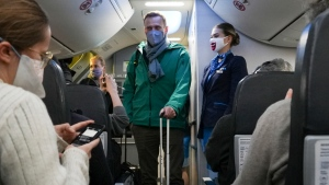Alexei Navalny and his wife Yulia board the plane prior to flight to Moscow in the Airport Berlin Brandenburg (BER) in Schoenefeld, near Berlin, Germany, Sunday, Jan. 17, 2021. Leading Kremlin critic Alexei Navalny flew home to Russia on Sunday after recovering in Germany from his poisoning in August with a nerve agent. (AP Photo/Mstyslav Chernov)
