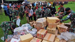 Indonesian soldiers distribute relief goods for those affected by the earthquake at a stadium in Mamuju, West Sulawesi, Indonesia, Sunday, Jan. 17, 2021. Rescuers retrieved more bodies from the rubble of homes and buildings toppled by the 6.2 magnitude earthquake while military engineers managed to reopen ruptured roads to clear access for aid relief goods. (AP Photo/Daeng Mansur)