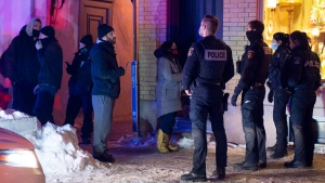 Quebec City police officers contain a handful of protestors as a curfew begins in the province of Quebec to counter the spread of COVID-19 on Saturday, January 9, 2021 in Quebec City. A handful of demonstrators walked downtown to protest the curfew. THE CANADIAN PRESS/Jacques Boissinot